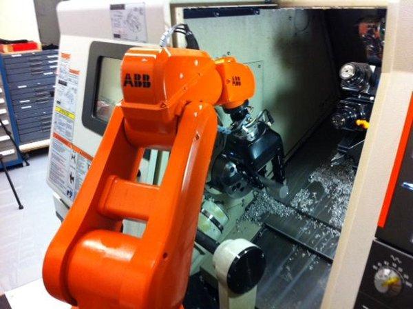 A robot feeding a CNC lathe using a 3-Finger Adaptive Gripper