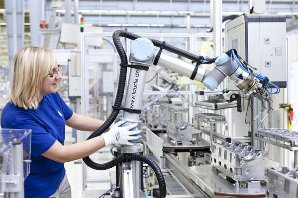 Human working with a cobot in a factory