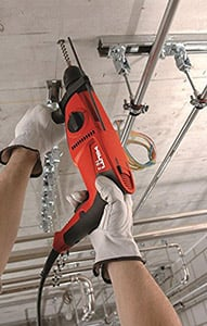 Worker drilling anchor holes on a ceiling