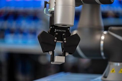 Robotiq 2F-85 cobot gripper picking a raw part with a parallel grip.